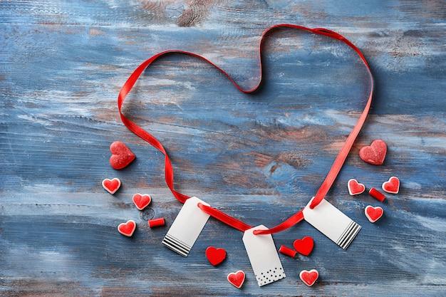 Лента в форме сердца с бирками и желейными конфетами на цветном деревянном фоне