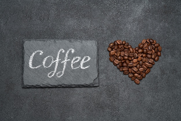 Heart shaped roasted coffee beans and handwritten sign on dark concrete table