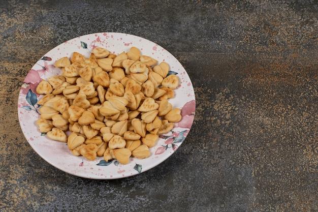 Cracker salati a forma di cuore sul piatto colorato.