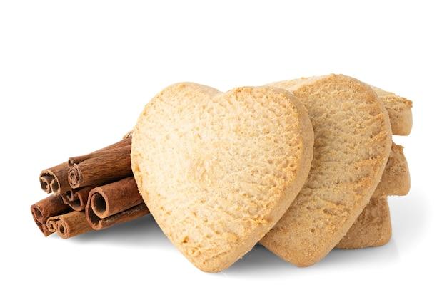 Песочное печенье и корица в форме сердца на белом фоне