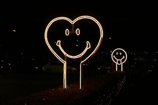 밤에 길가에 심장 모양의 웃는 얼굴 네온 사인