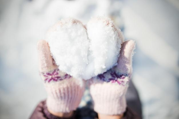女性の手のハート型の雪