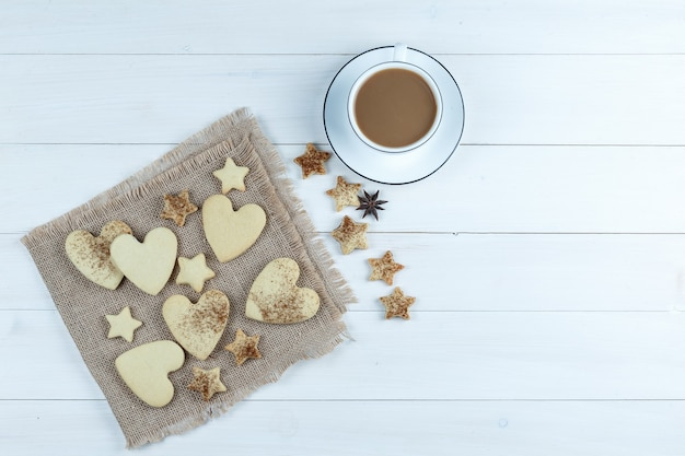 Heart-shaped and star cookies on a piece of sack with star cookies, cup of coffee flat lay on a white wooden board background