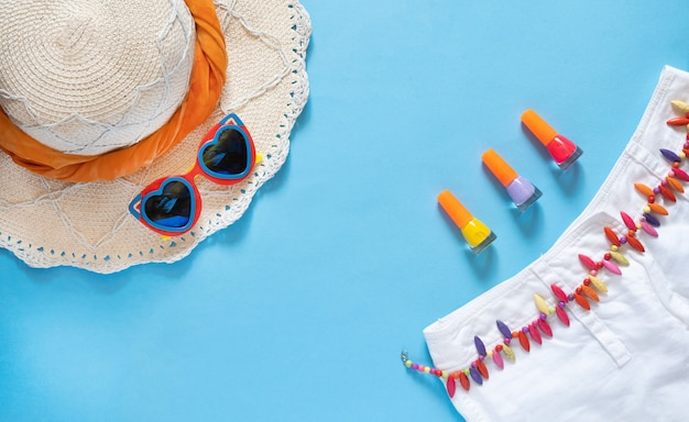 Heart shaped sunglasses, straw hat, shorts and nail polishes on blue background