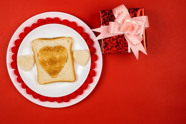 심장 모양의 흰색 세라믹 접시에 구운 된 호 밀 빵 조각에 토스트. 발렌타인 데이 개념. 아침 식사 디자인을 좋아합니다. 축제 점심 또는 아침 식사. 공간을 복사하십시오. 선물