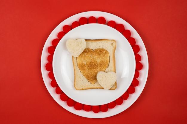 심장 모양의 흰색 세라믹 접시에 구운 된 호 밀 빵 조각에 토스트. 발렌타인 데이 개념. 아침 식사 디자인을 좋아합니다. 집에서 만드는 건강한 샌드위치. 축제 점심 또는 아침 식사. 공간을 복사하십시오.