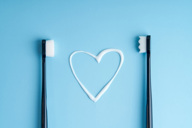 Heart shaped toothpaste between two toothbrushes.