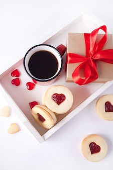 Heart shaped traditional linzer cookies with strawberry jam, mug of coffee and gift box on the white wooden tray. valentine s day concept. top view.