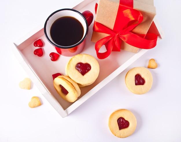 白い木製のトレイにイチゴジャム、コーヒーのマグカップ、ギフトボックスが付いたハート型の伝統的なリンツァークッキー。バレンタインデーのコンセプト。上面図。