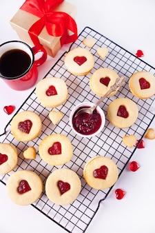 Традиционное линзерное печенье в форме сердца с клубничным вареньем. концепция дня святого валентина. вид сверху.