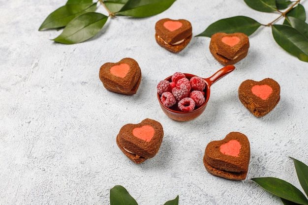 Heart shaped valentine cookies with frozen raspberries on light