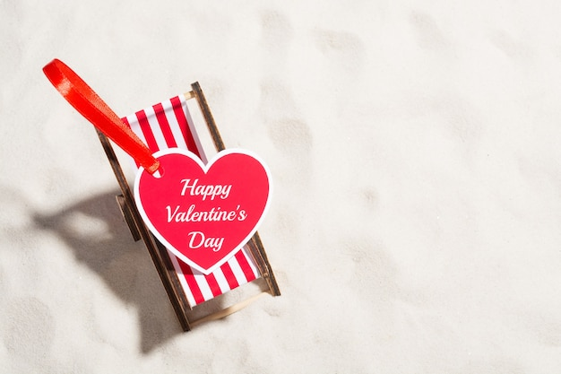 Heart-shaped valentine's day greeting card and small deckchair on the sand.