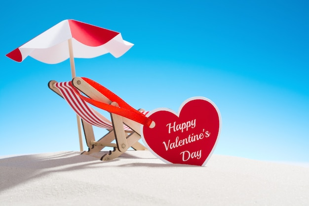 Heart-shaped valentine's day greeting card and small deckchair with umbrella on the sand.
