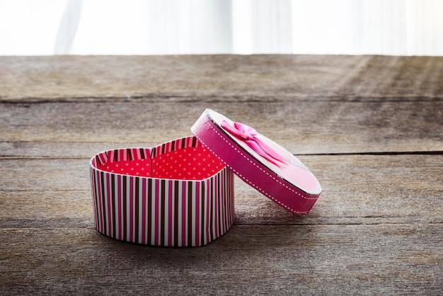 Подарочная коробка дня святого валентина сердечной формы на старых старинных деревянных пластинах. сладкий праздник фон