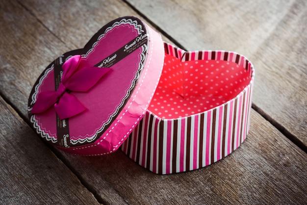 Подарочная коробка дня святого валентина сердечной формы на старых старинных деревянных пластинах.
