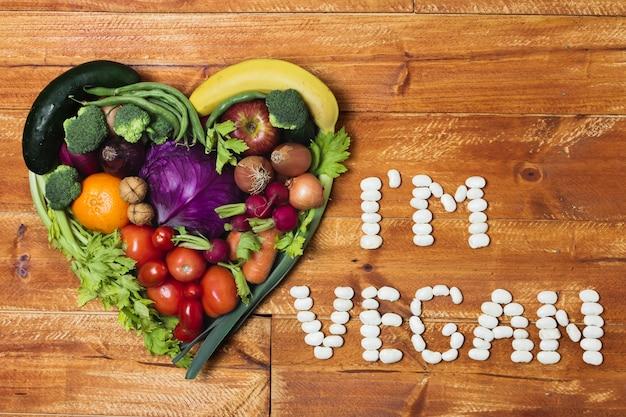 Disposizione di verdure a forma di cuore su fondo di legno