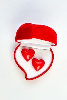 심장 모양의 장식 하트와 벨벳 상자. 귀걸이, 평면도와 하트 모양의 선물 상자를 열었습니다. 발렌타인 데이 휴가 개념.