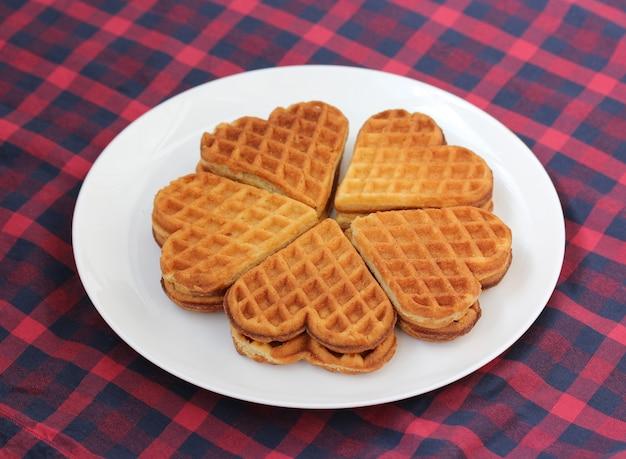 Вафли в форме сердца в белой тарелке на красной клетчатой скатерти, десерт.