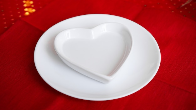 Heart shaped white plate on red
