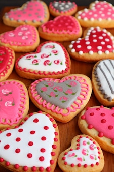 Heart shaped with lovely pattern cookies laid out on wooden tray