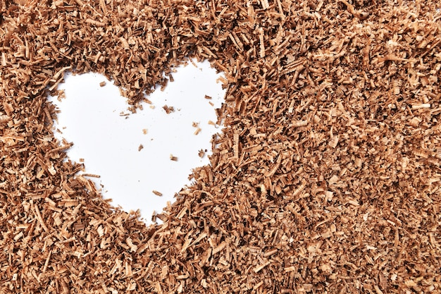 Heart-shaped and wood saw dust on dirty white background