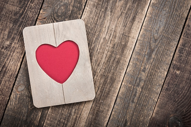 Heart shaped wooden frame on wooden boards
