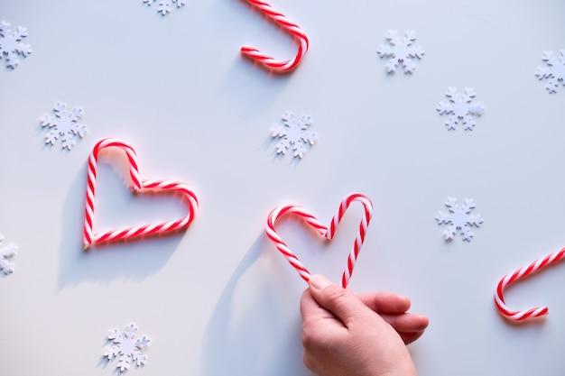 Формы сердца из леденцов, красно-белые пятнистые безделушки на белой ткани.