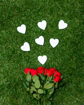 Heart shapes and roses bouquet on green grass.