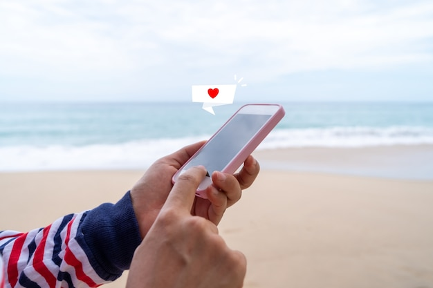 Heart sign on chat box icon on smartphone at summer beach technology.
