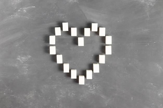 Знак сердца, выложенный из кусков сахара на сером фоне ко всемирному дню борьбы с диабетом 4 ноября