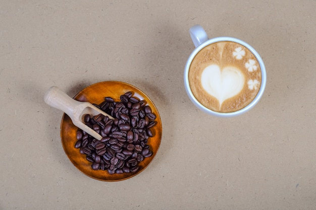 Heart sign on late art coffee with fresh coffee bean on table.