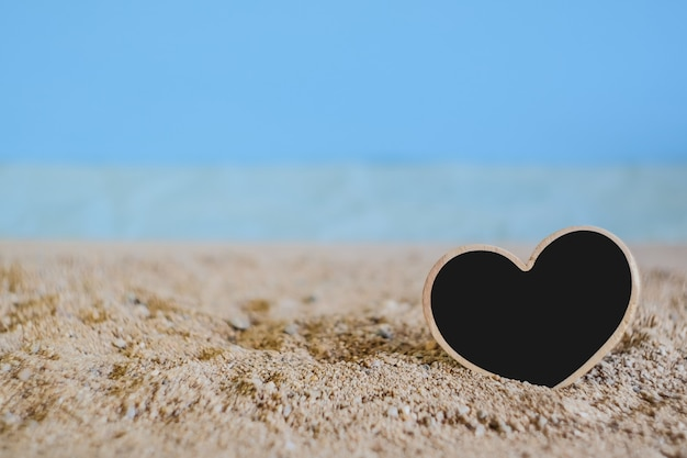 Heart sign wood with tropical sand beach ,love concept and soft focus.