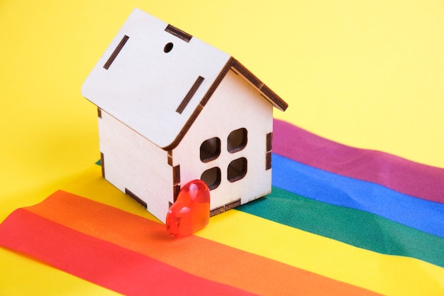 Heart and small house on the lgbt flag, yellow background, copy space