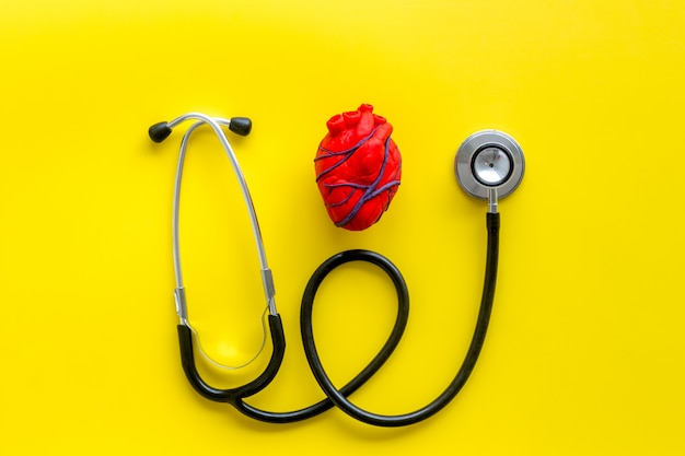 Heart and stethoscope isolated on yellow