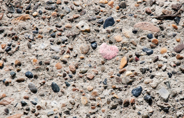 Heart of stone between multi colored natural stones background