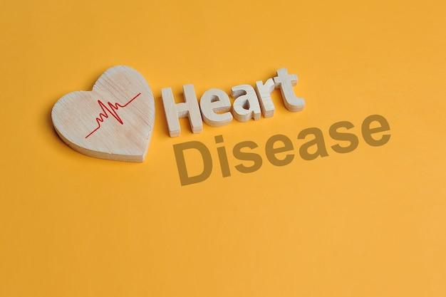 노란색 배경에 고립 된 나무에서 만든 심장 기호 및 심장 텍스트
