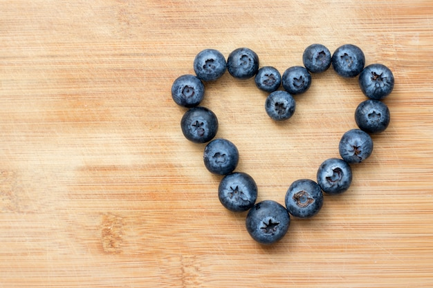 Heart symbol formed with blueberries on wooden