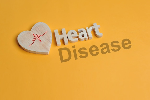 Heart symbol and heart text created off wood isolated on yellow background