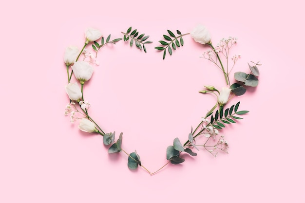 Heart symbol made of flowers and leaves on pink.