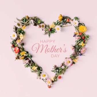 白い表面に幸せな母の日のテキストとfloversと葉で作られたハートのシンボル