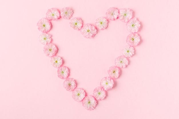 パステルピンクの背景にピンクの花の春の花で作られたハートのシンボル。愛の概念。フラットレイ。上面図。バレンタインデーの背景