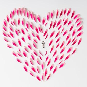 Символ сердца из розовых цветочных лепестков со старым ключом