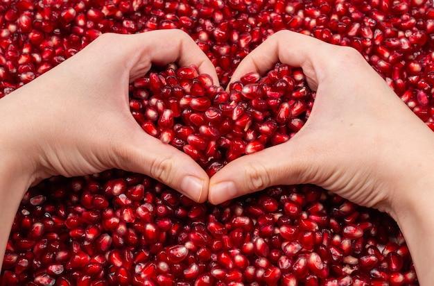 Символ сердца. семена граната в руке женщины.