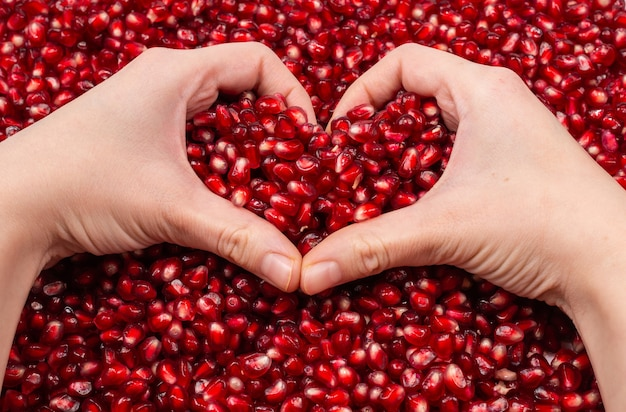 Heart symbol. pomegranate seeds in woman hand.
