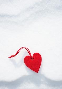 Игрушка сердце на фоне снега