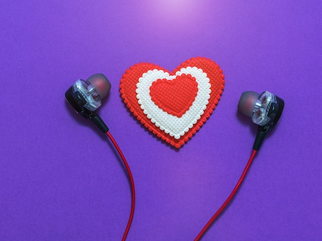 Heart of white and red colors in earphones on purple background. rendered image. flat lay.