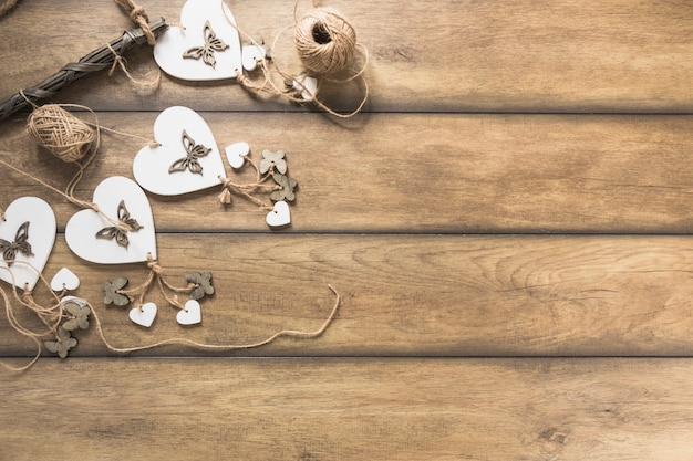Heart windchimes on wooden plank with spool