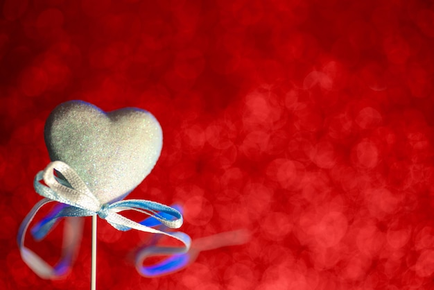 A heart with a bow. red blurred bokeh in the background. the concept for valentine's day