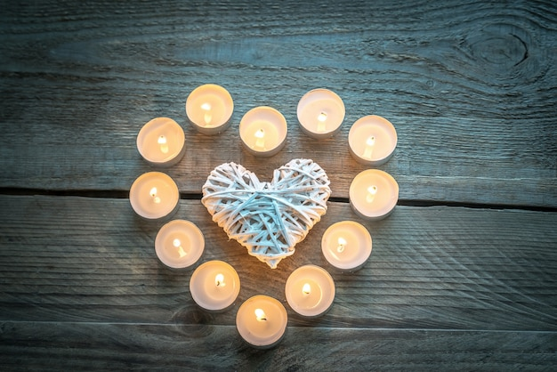 Heart with burning candles on the wooden table