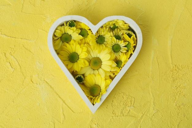 黄色のテクスチャ背景に菊のハート。